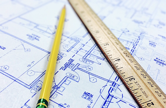 Blueprints with ruler and yellow pencil